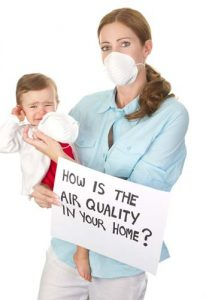 woman holding a small child and wearing a dust mask
