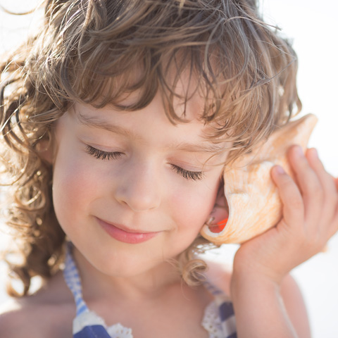 child listening to a sea shell