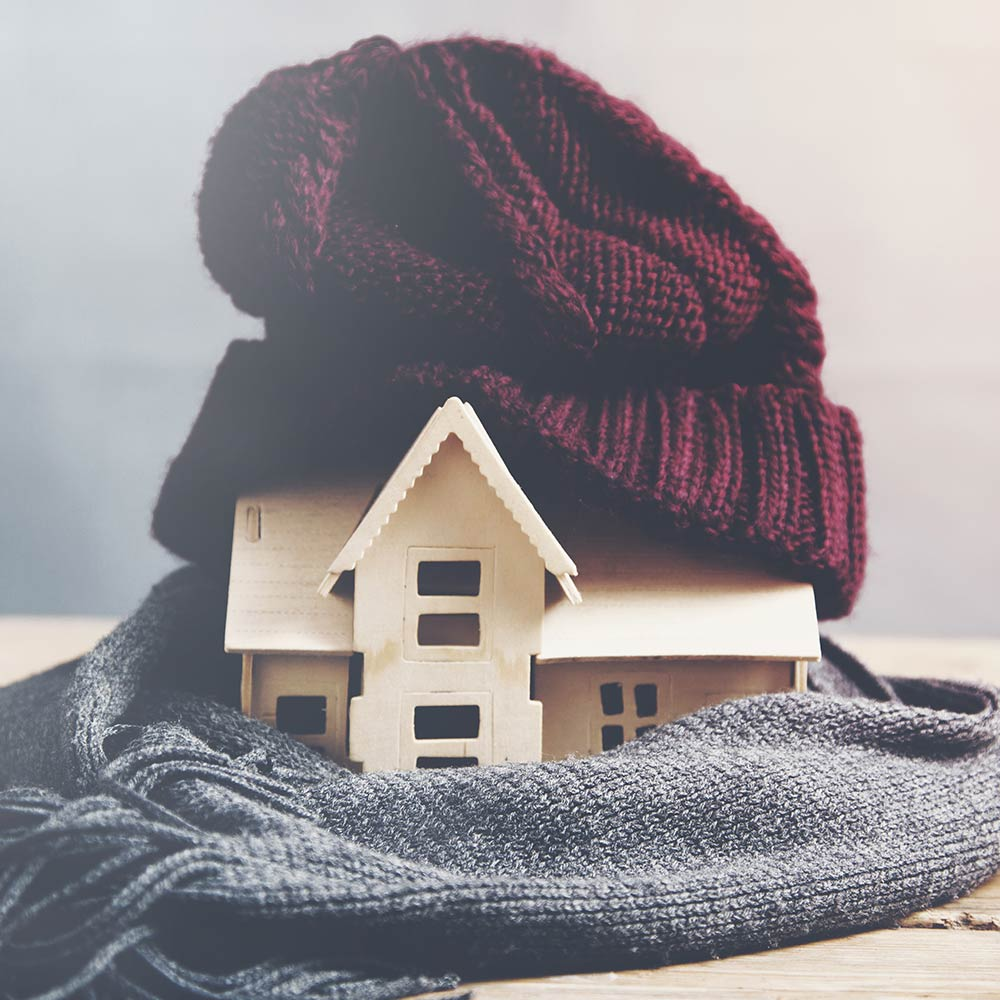 Awooden model of a house wrapped in a scarf and knit hat