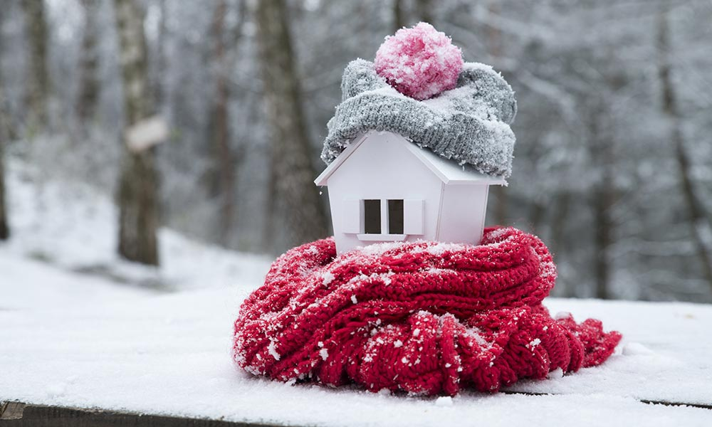 toy house with a kit hat and scarf around it.